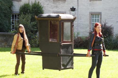 Professor Alice Roberts and a colleague carry a chair in Edinburgh for the programme