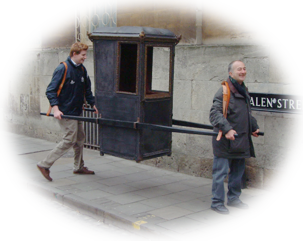 Sir Tony Robinson (front) carries the speaker's chair though Oxford